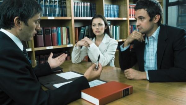 Et par som har boligkjøperforsikring diskuterer med en advokat etter at de fant muggsopp i boligen