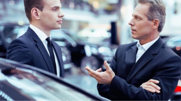 En mann som er misfornøyd med bilkjøpet og snakker med selgeren