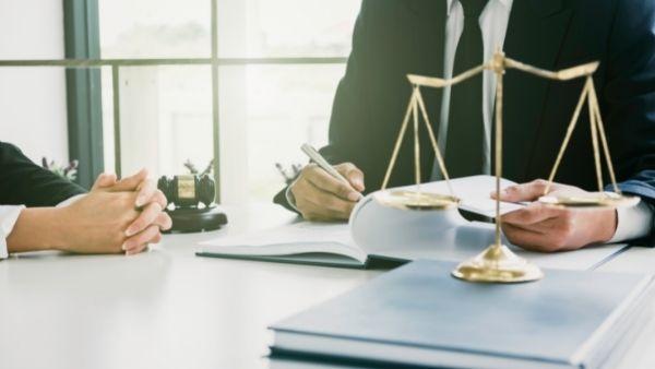 En advokat og en klient som diskuterer om menererstatning